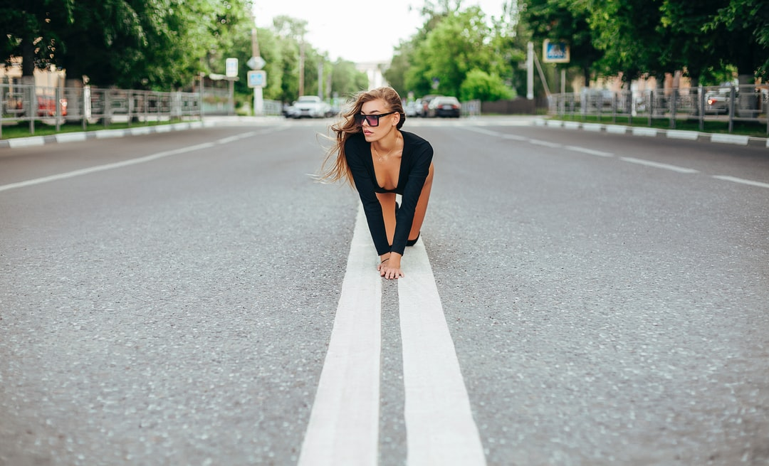 A woman standing on the side of a road